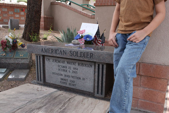Connor Love stands by the graveside of Army Cpl. Jeremiah W. Robinson in Mariposa Gardens Memorial Park in Mesa, Ariz. Love frequents the memorial garden to honor fallen soldiers and make sure Robinson's gravesite is kept clean.(Photo by Asha Anchan, News21)