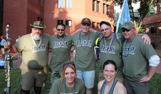 Top from left to right: Ruck Up members and Veterans AJ Paige, Nicholas Leone, Don Spencer, Eddie Brown and John Pajak pose for a photo with team member (bottom) Sue Barton, and Miles for Military  team member and veteran Angie Guss. These seven participated in the Out of the Darkness Overnight Walk in Washington, D.C. The 16 to 18-mile walk is held each year in a different city by the American Foundation for Suicide Prevention to raise money for suicide prevention efforts. This year's walk attracted about 1700 walkers and 300 volunteers. (Photo by Chase Cook, News21)