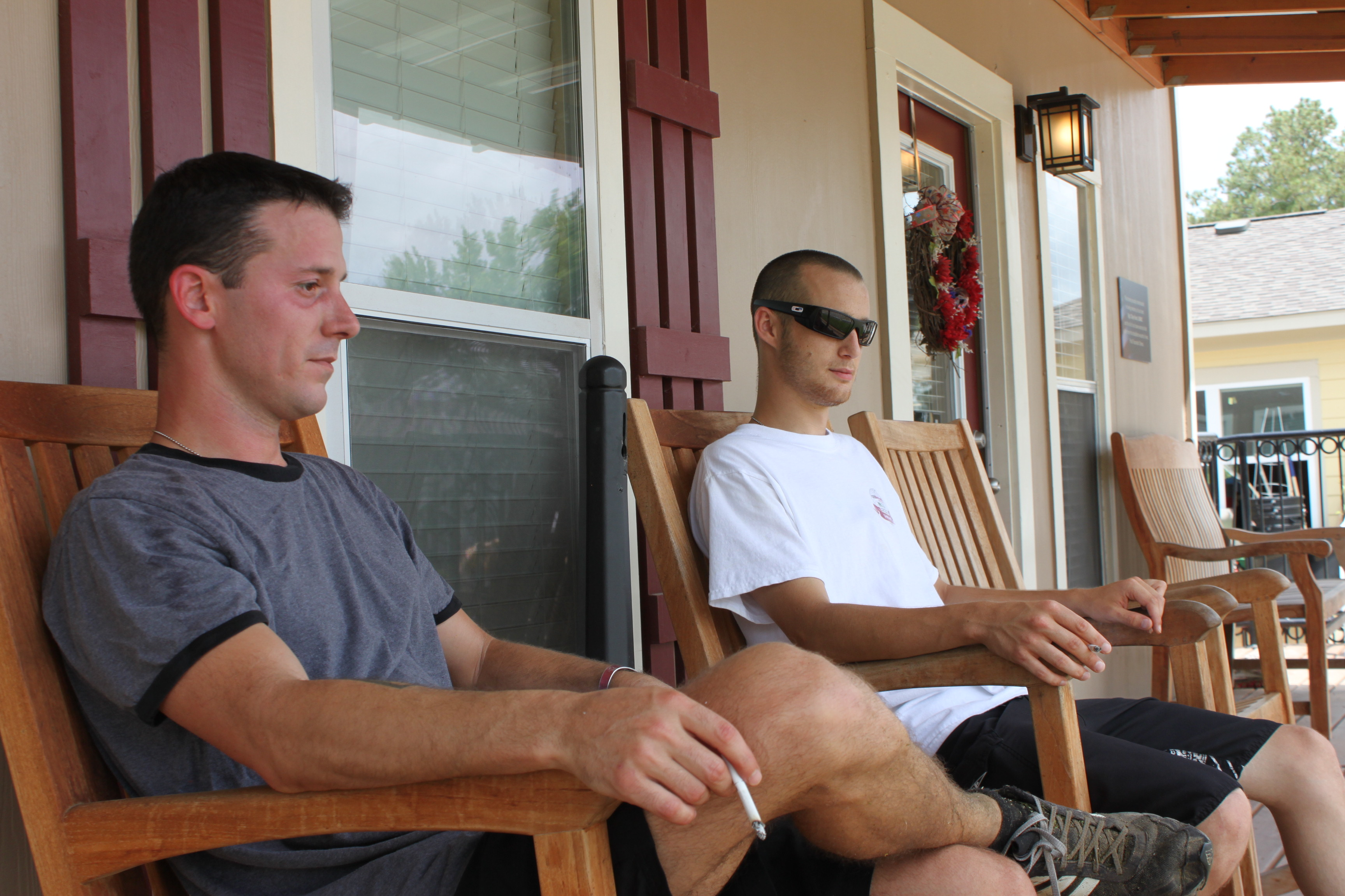 Matthew XXXXX smokes cigarettes with Jaydee Faulkner at their interim house on June 25th, which is part of the PTSD Foundation of America's Camp Hope in Houston, Texas. The camp offers housing for struggling veterans, like Faulkner who suffers from post-traumatic stress brought on by his service in the Army. (Photo by Chase Cook, News21)