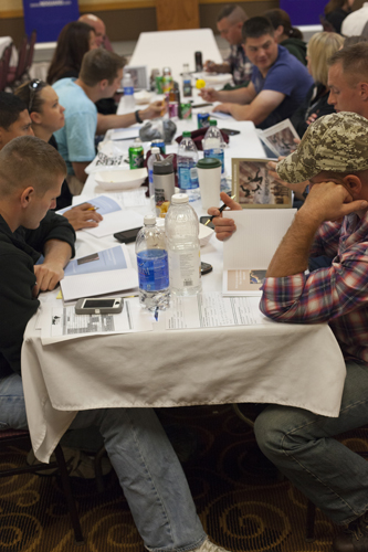 "North Dakota National Guard members from the 818th Engineer Company write in their ""Brothers at War"" journals after watching the film. The workshop incites conversations about being at war, coming home and relating to family. (Photo by Peter Haden, News21)"